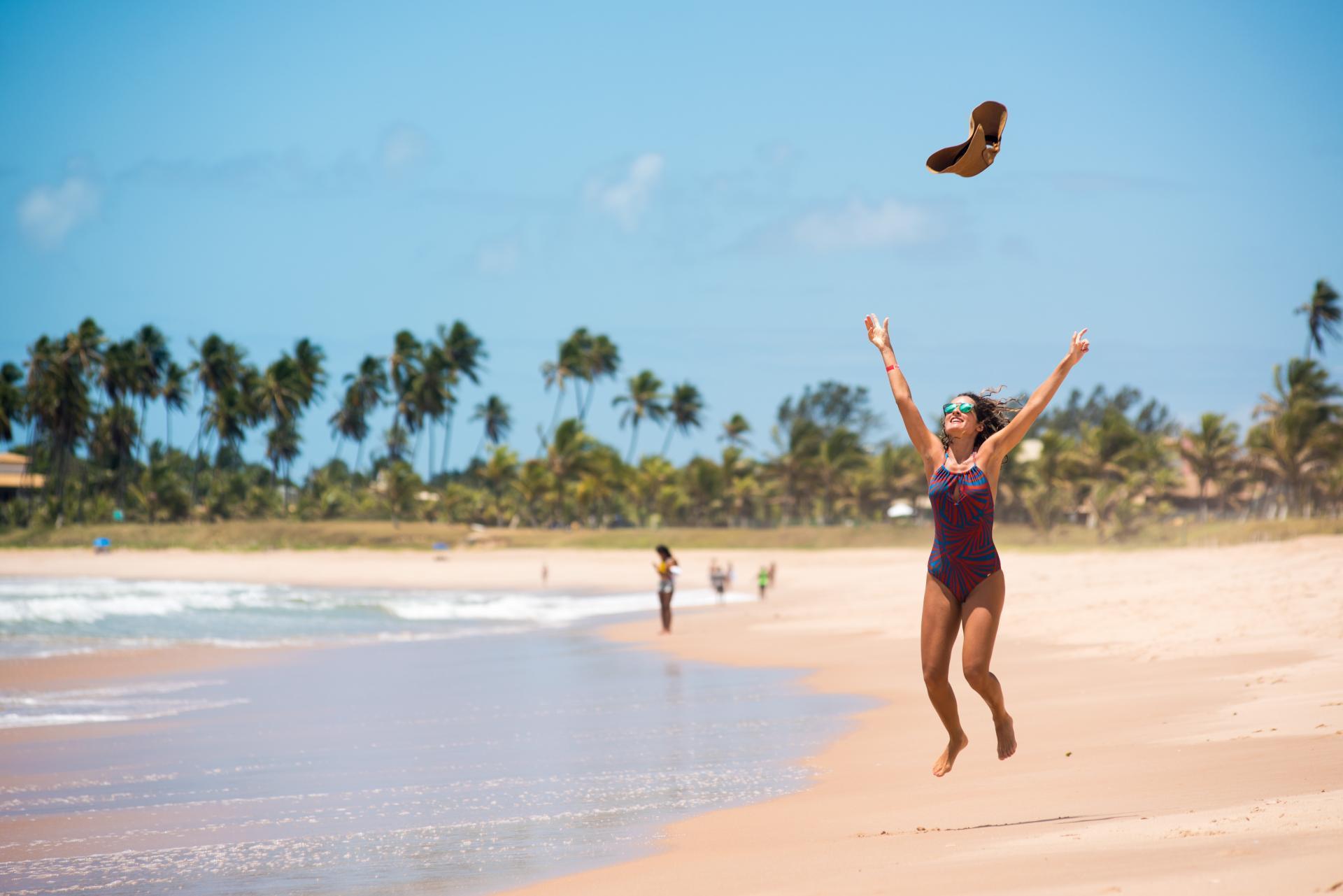 A vacationer takes a joyful leap at Guarajuba beach.