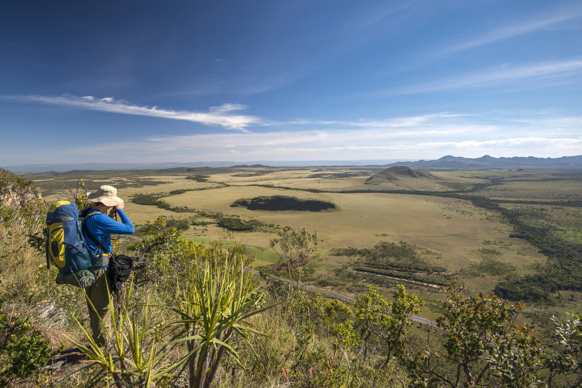 An eco-tourist enjoys the extensive view in Chapada dos Veadeiros.