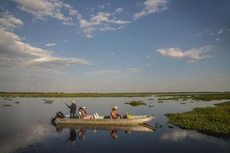 Three visitors fishing in a motorboat on a river of the North Pantanal