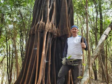 Guest posing in front of a huge trunk in the Amazon Rainforest