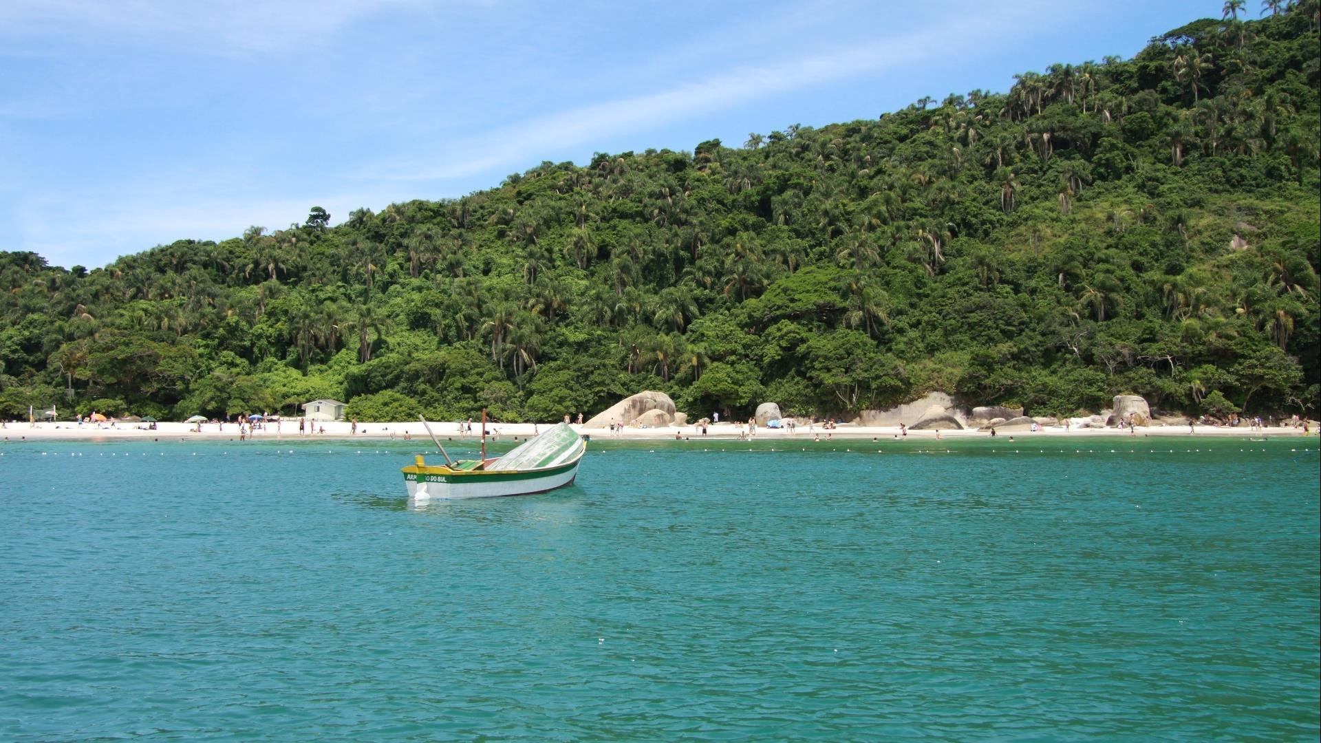 A boat on the green sea and in front of a lonly beach, surounded by Atlantic Rainforest