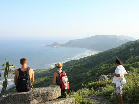 Three visitors enjoying the view during a hike in Florianopolis