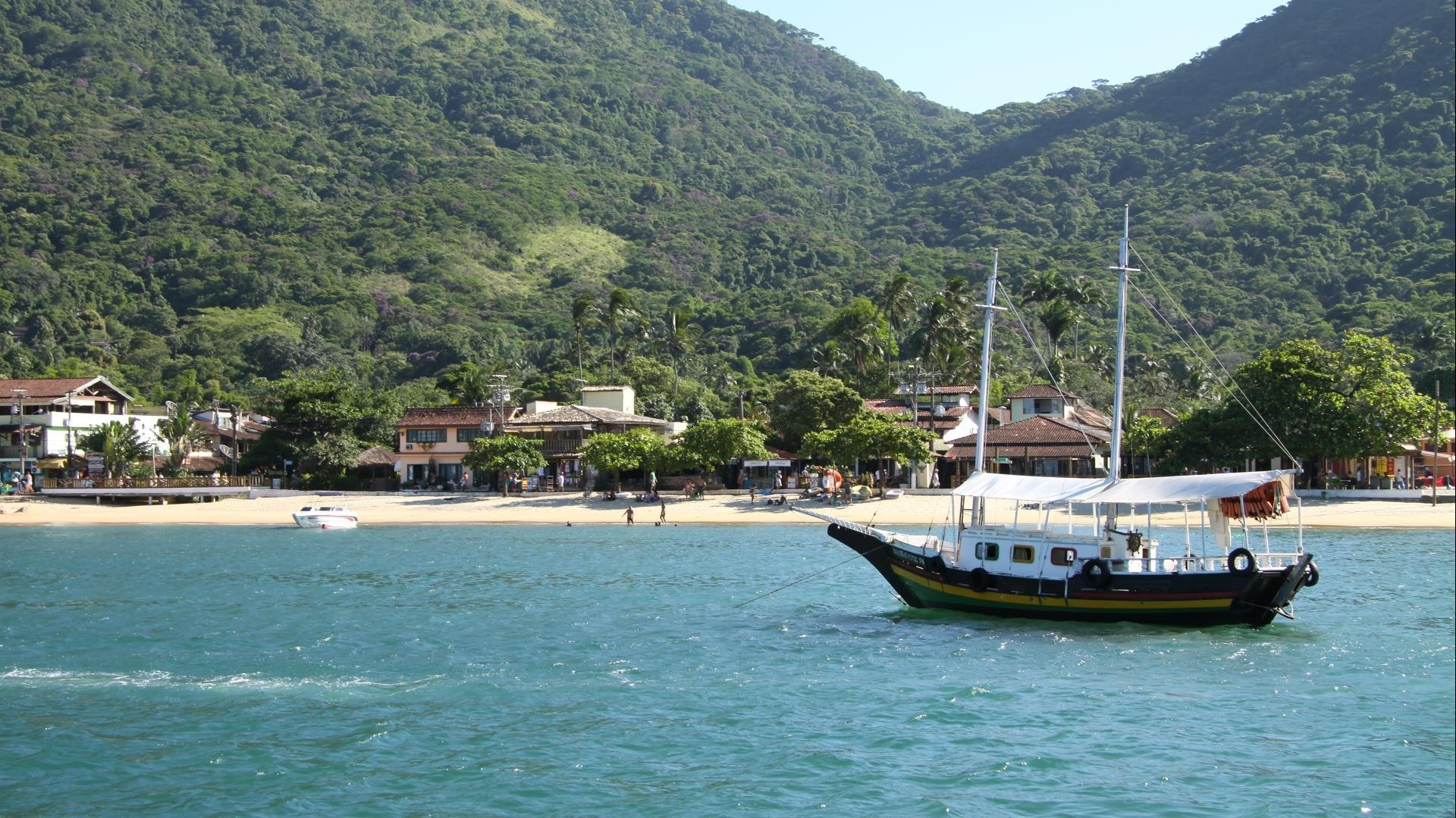 A typical boat in front of a beach and Atlantic Rainforest of Ilha Grande, Rio de Janeiro