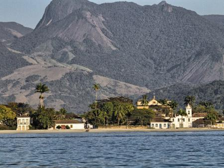 A nice view from a boat on colonial buildings in front of the mountains