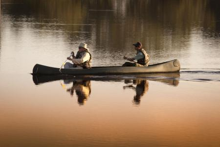 A guide and a visitor in a canoe during a trip near by Caiman Lodge