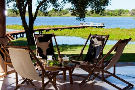 A table with four chairs and a nice view on the river at Caiman Lodge