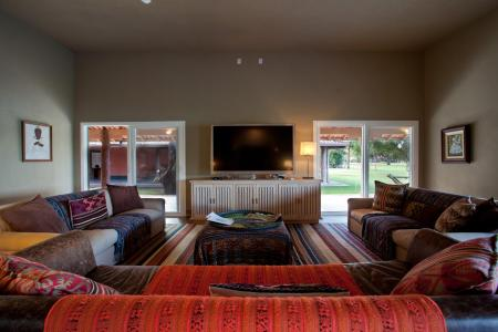 Living room with TV and Sofas, at Caiman Lodge
