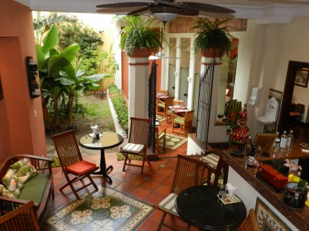 The bar with seats, tables and an outdoor area at Hotel Casa do Amarelindo