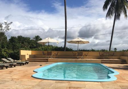 A pool with palm trees at Pousada Tapera in Itubera, Bahia