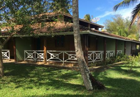 Palm trees, lush green gardens and the main building of Pousada Tapera in Itubera, Bahia