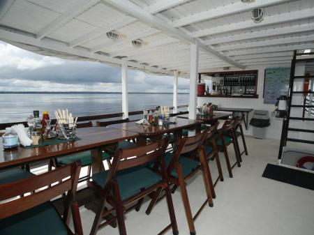The upper deck with tables and seats for dinning at the Amazon Clipper